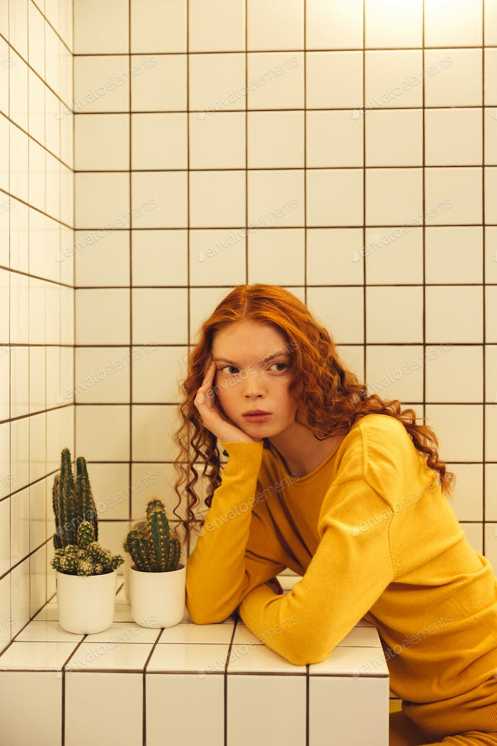Concentrated young redhead curly lady sitting in cafe