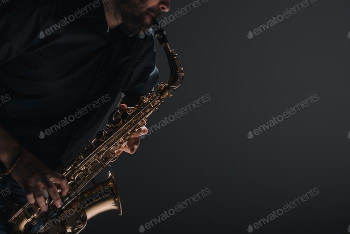 cropped shot of jazzman playing saxophone on black