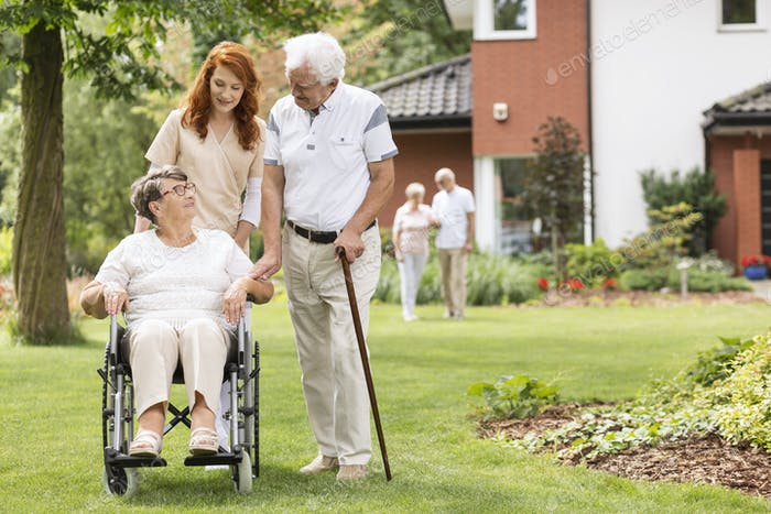 An elderly disabled couple with their caretaker in the garden ou