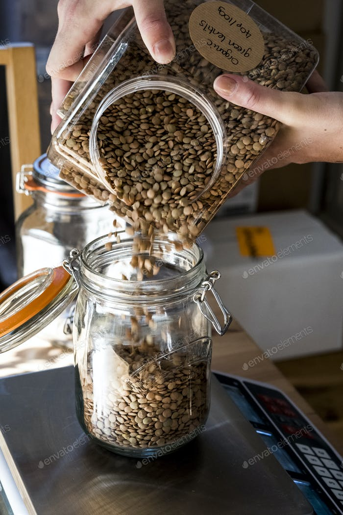 Close up of person pouring brown lentils into glass jar on kitchen scales.