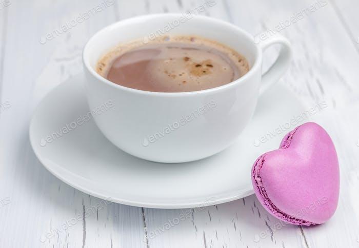Eine Tasse heiße Schokolade mit einem herzförmigen Macaron