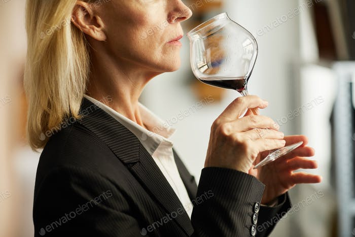 Mature Woman Tasting Wine Closeup