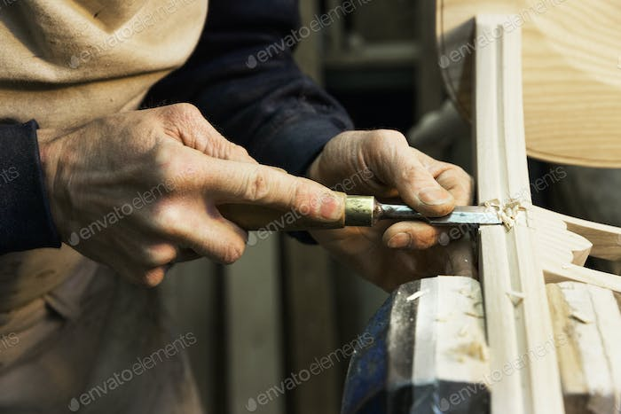 Man at a work bench in a carpentry workshop with a chisel.