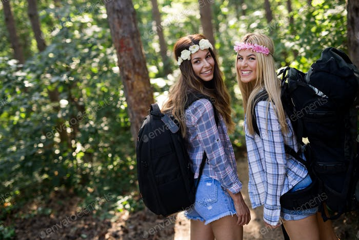 Adventure, travel, tourism, hike and people concept. Happy women with backpacks in forest