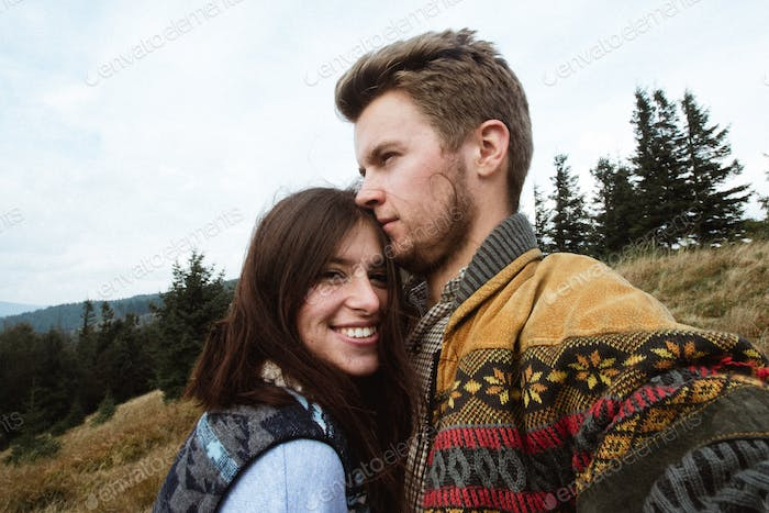 stylish beautiful traveling tender happy couple in the mountains on a background of a forest