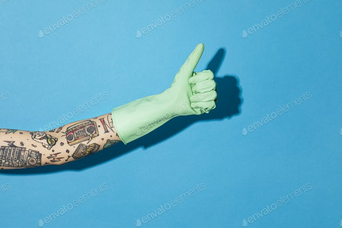 Tattooed hand thumbs up in a rubber glove