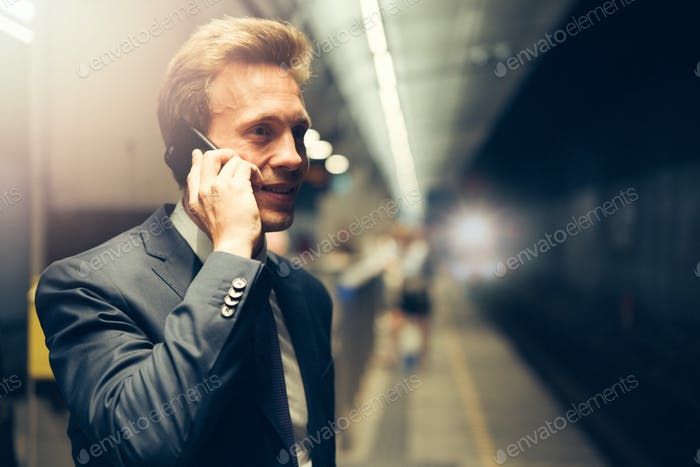 Executive standing on a subway platform talking on a cellphone
