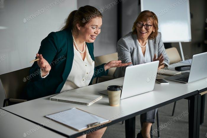 Freudiger Mitarbeiter schaut auf Laptop-Bildschirm