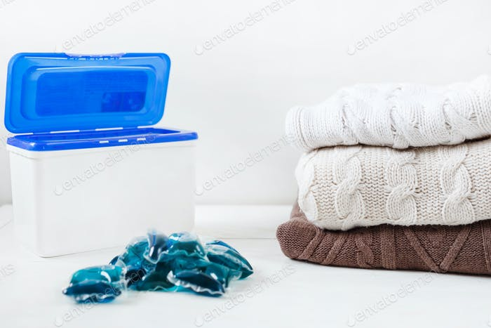Box with detergent laundry capsules with gel for washing and a stack of wool sweaters.