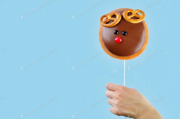 Donut in hand on a blue background