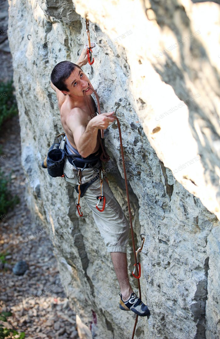 Rock climber struggling to make the next movement