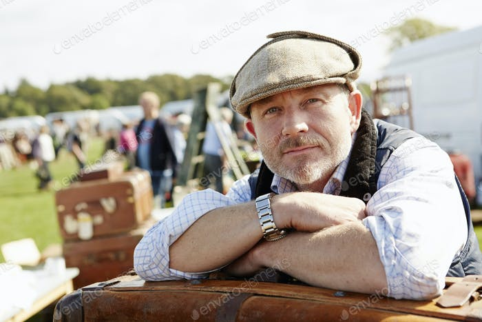 Smiling man wearing a flat cap at a flea market, a trader resting leaning on a pilke of cases