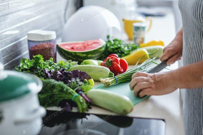 Mujer cocinar verduras en la cocina