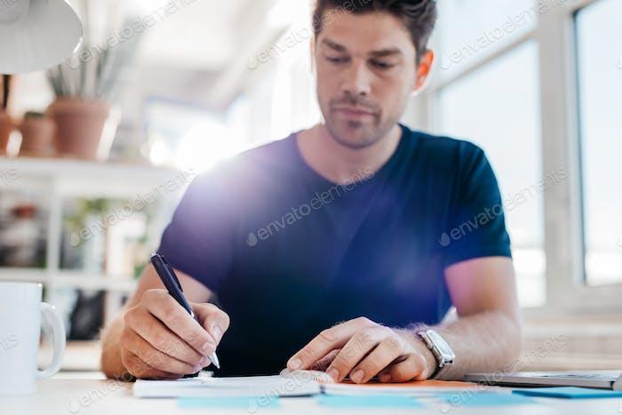 Junger Geschäftsmann Aktualisierung seiner persönlichen Organisator
