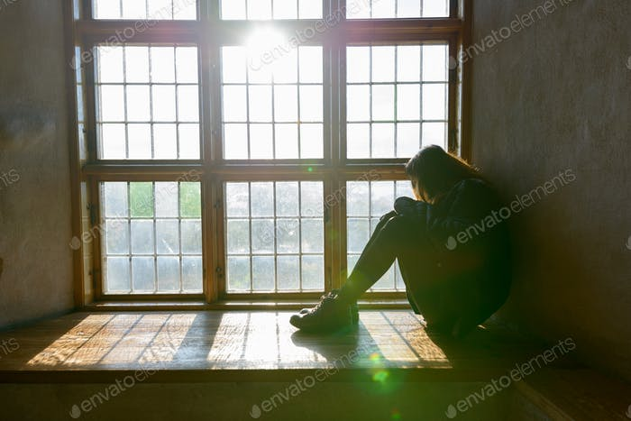 Young woman sitting in front of closed wooden window with sunlight streaming in