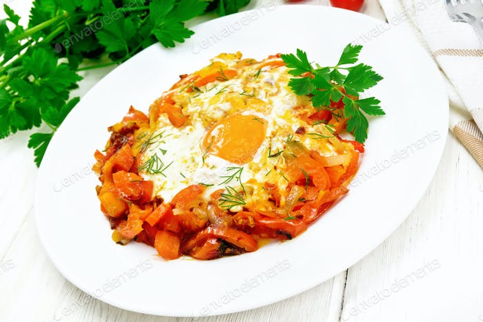 Scrambled eggs with vegetables in plate on light board