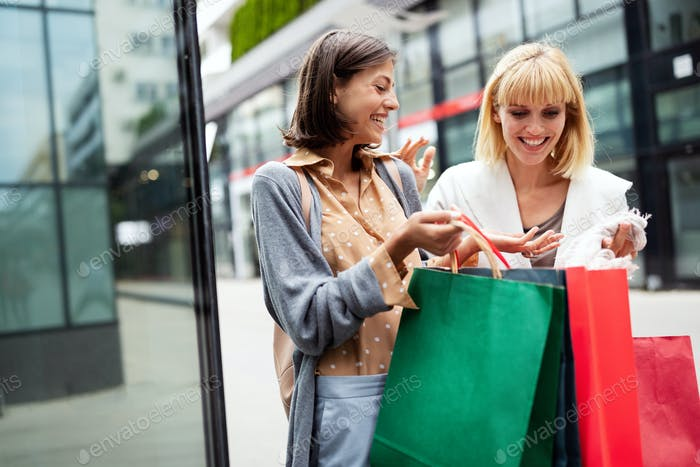 Shopping and tourism concept. Beautiful women with shopping bags in ctiy having fun