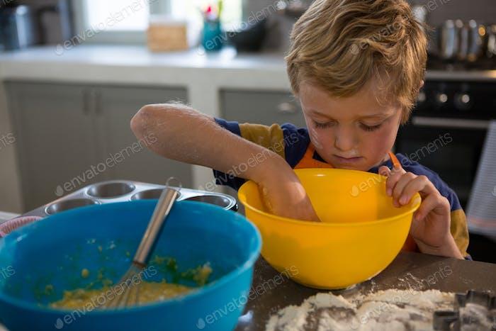 Boy preparing food in yellow bowl