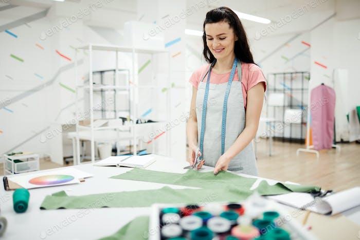Positive female dressmaker in own studio