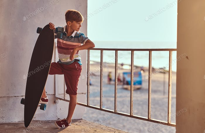 Young skater boy in shirt and shorts outdoors
