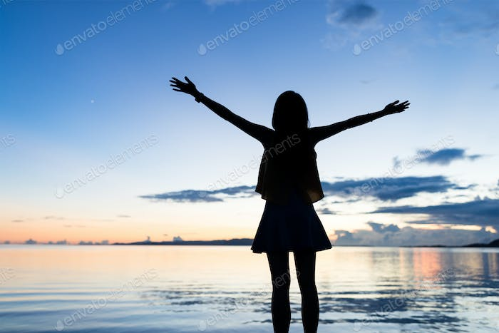 Silhouette of woman raising hand at sunset time
