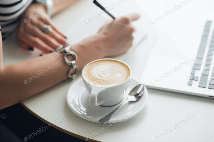 Hot art Latte Coffee in a cup on wooden table and Coffee shop blur background with woman's hands.