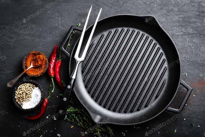 Leere gusseiserne Grillpfanne mit Zutaten zum Kochen auf schwarzem Hintergrund, Draufsicht