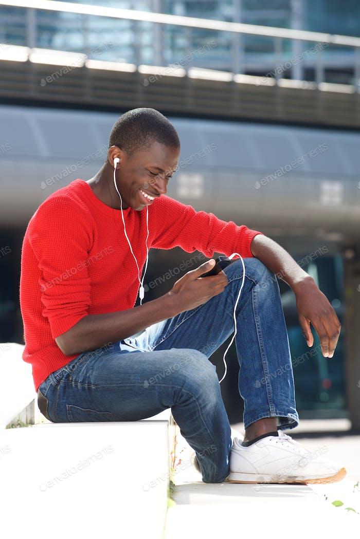 Joven africano Hombre escuchando música al aire libre