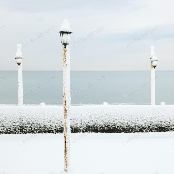 Lamp covered by snow on ocean beach in winter
