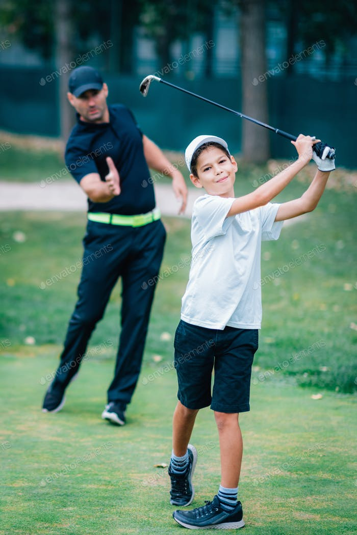 Personal Golf Lessons. Golf Instructor Adjusting Swing of a Young Boy.