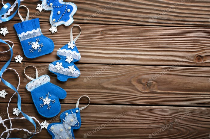 Handmade rustic felt Christmas tree decorations flat laying on w