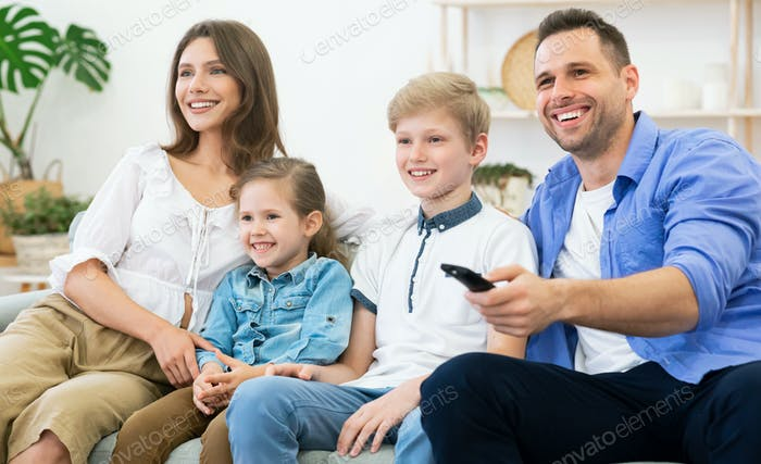 Happy Parents And Kids Watching TV Together Sitting At Home