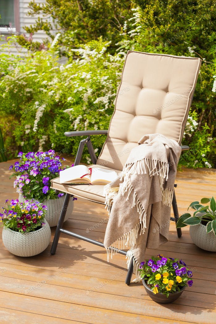 garden chair on terrace in sunlight, flowers bush