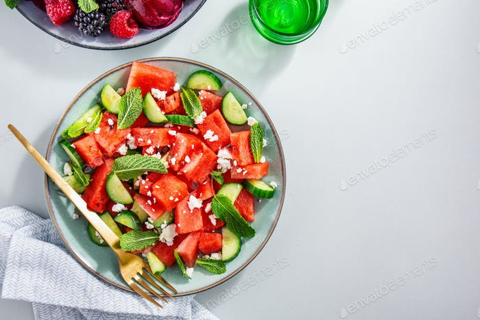 Summer salads with watermelon and cucumbers, berries and ice cre