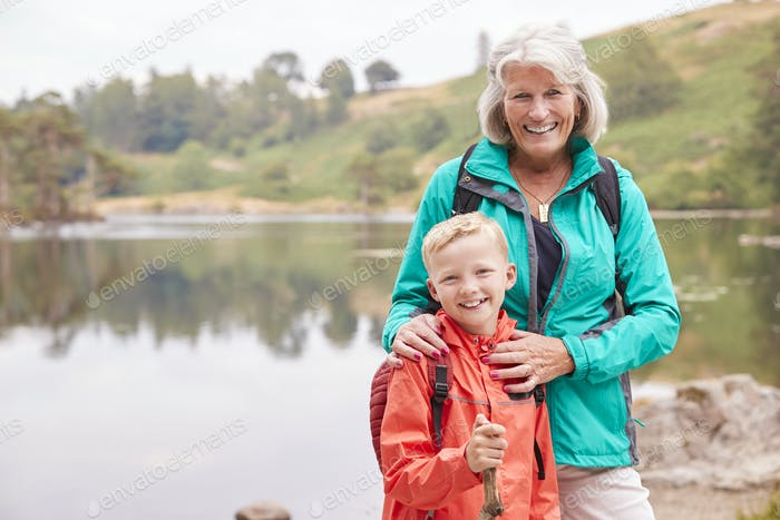 Grandmother and grandson standing together near a lake in the countryside smiling to camera