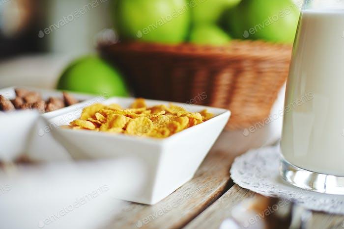 Muesli, fresh milk and apples with beautiful bokeh