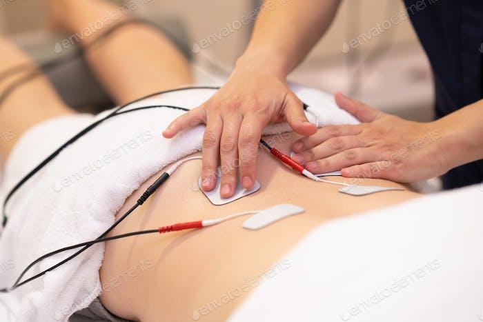 Elektro- stimulation in der Physiotherapie für eine junge Frau