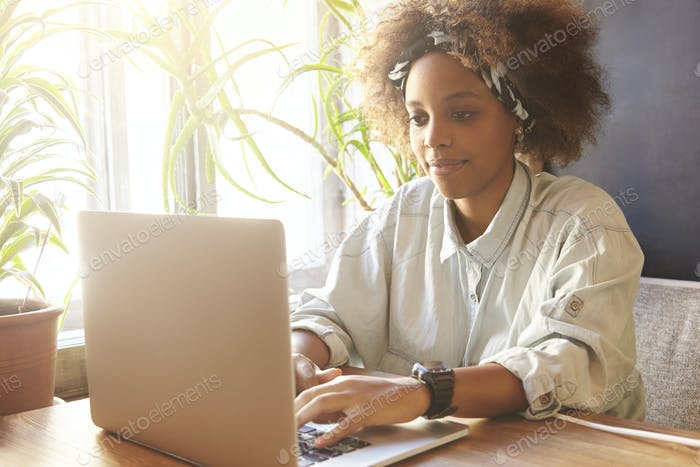 Human and technology. Young stylish dark-skinned woman typing on laptop, texting friends via social