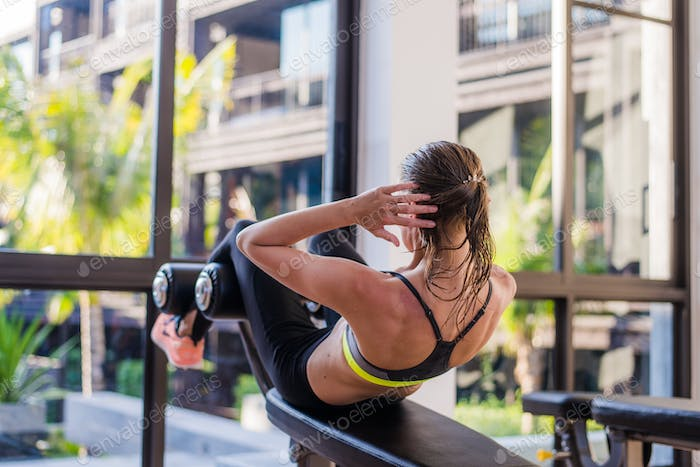 portrait of an athletic woman doing exercising abdominals work-out lying in gym at luxury hotel at