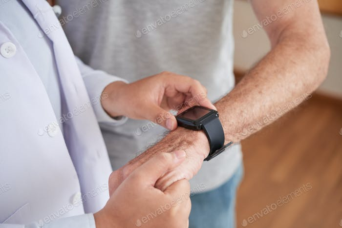 Doctor measuring pulse of patient with smart watch