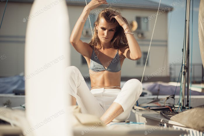 Posh woman in swimsuit white trousers and modern jewelry sensually looking in camera sitting on boat