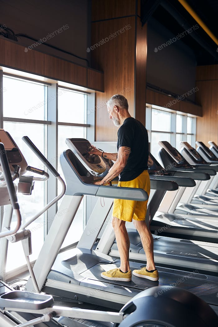 Man setting the control panel on the treadmill