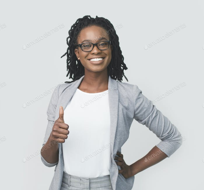 Cheerful Black Businesswoman Gesturing Thumbs-Up, On White Background In Studio
