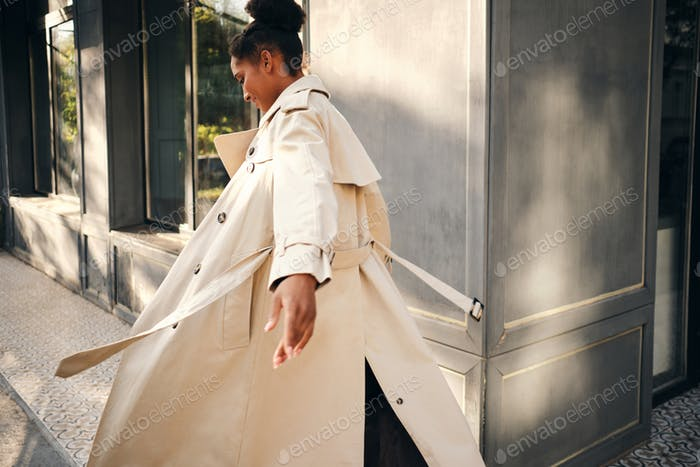 Attractive casual African American girl in stylish trench coat dreamily whirling on city street