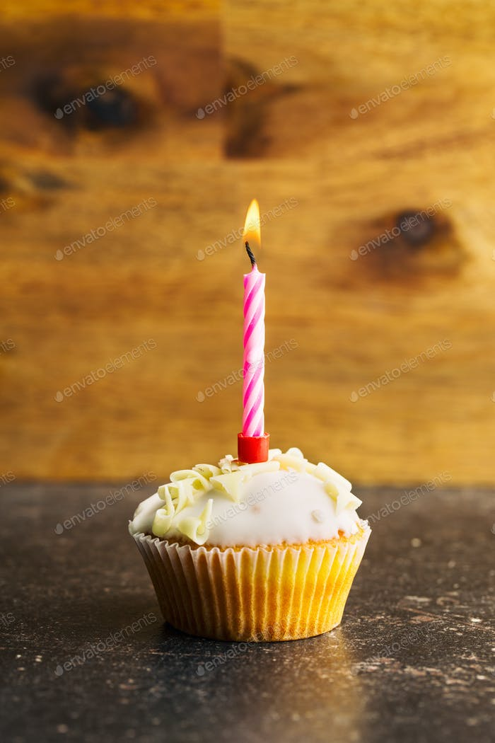 Cupcake with burning candle.