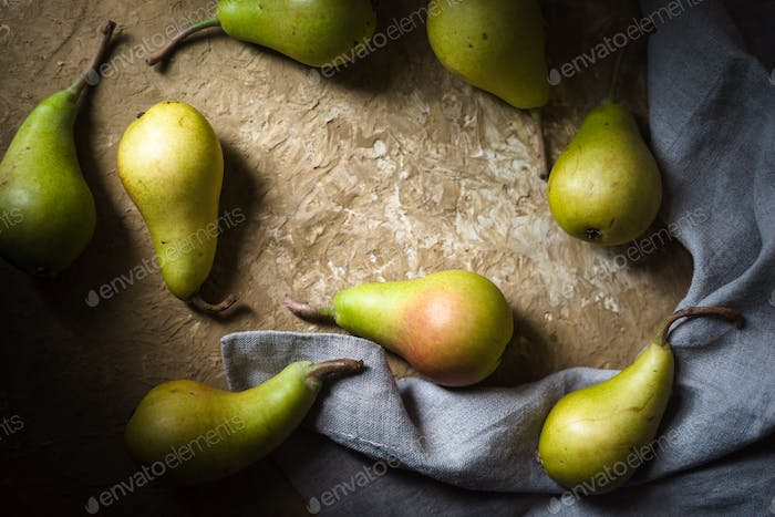 Ripe pears, gray napkin on a green table