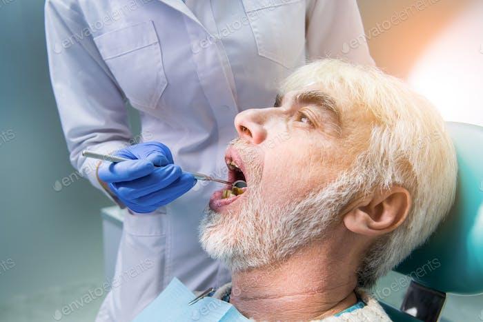 Dentist with mirror examining patient