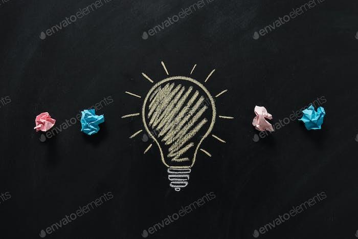 Draufsicht auf Papiermüll mit auf Tafel gezogener Glühbirne