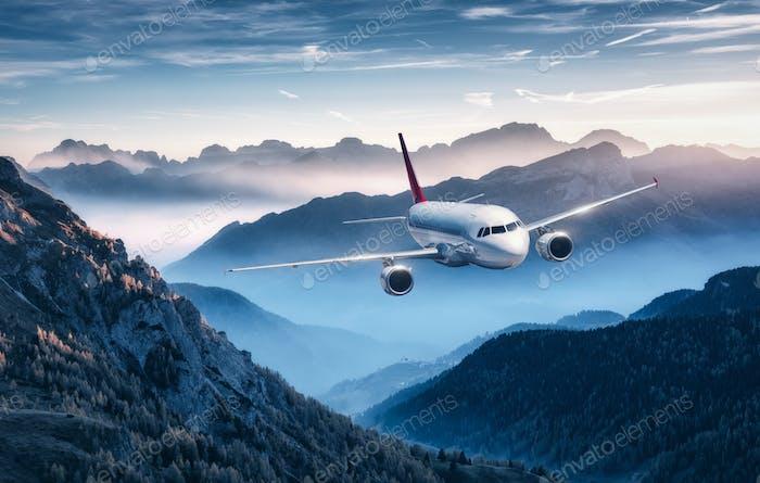Flugzeug fliegt über Berge im Nebel bei farbenfrohen Sonnenuntergang