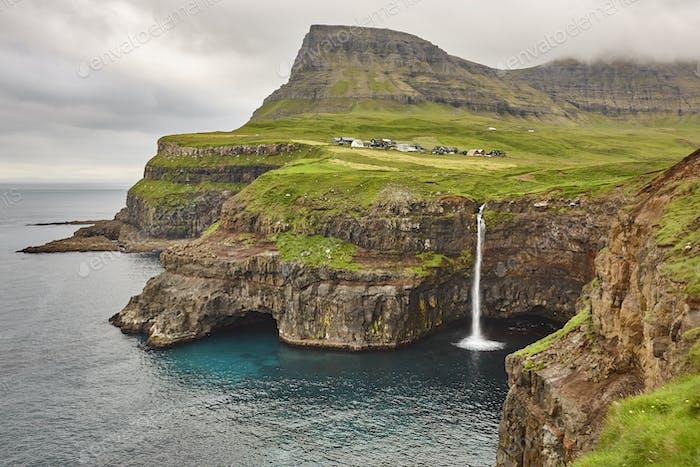 Waterfall and cliffs on Vagar. Faroe Islands dramatic coastline. Gasaladur